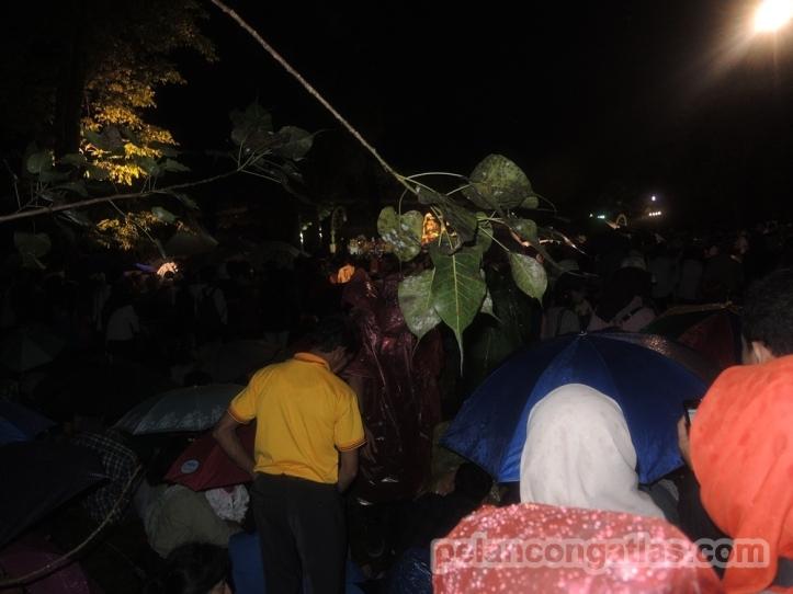 Setia menunggu di depan panggung sambil hujan-hujanan.